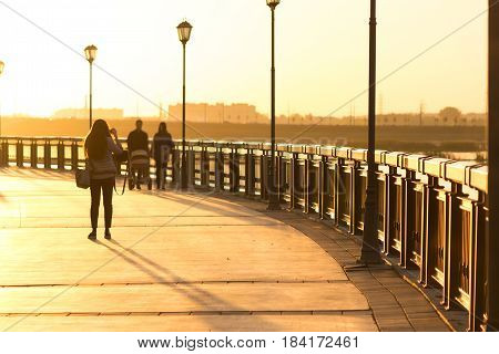 Silhouettes of people walking along the seafront promenade