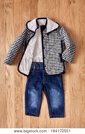 Children's jeans and jacket on wooden background. Checkered jacket with hood and blue dark jeans. Clothes for little boy. Casual and modern chidren's style.
