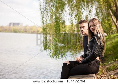 Couple on th edge of lake posing at camera. In love and relationship. Happines and love