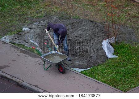 Construction worker pushing a wheelbarrow on the street