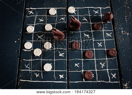 Checkers drawing on wooden table. Ancient Intellectual board game. Chess board. White and brown chips.