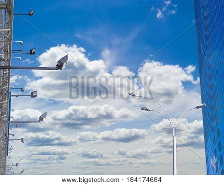 Many light fixtures for billboard backlighting pole of a street lighting and fragment of the modern multistory office building against the background of sky with clouds in daytime