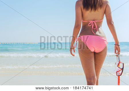 Beach vacation snorkel girl snorkeling with mask and fins. Bikini woman relaxing on summer tropical getaway doing snorkeling activity with snorkel tuba and flippers sun tanning. Suntan skin body care.