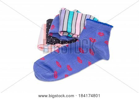 Blue women's sock against of the stack of other different varicolored socks on a light background