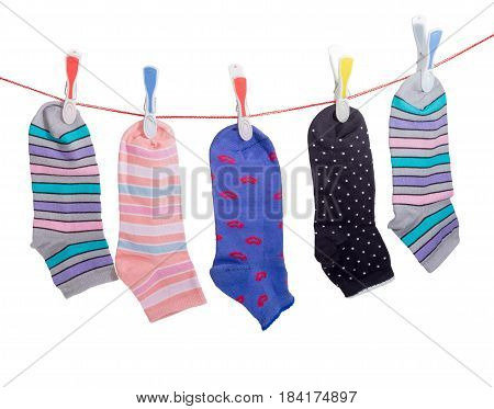 Several different varicolored women's socks hanging on the clothes line with plastic clothespins on a light background