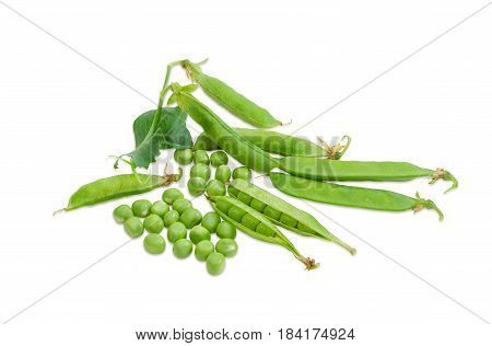Fresh green peas shelled from the pods and several pea pods on a light background