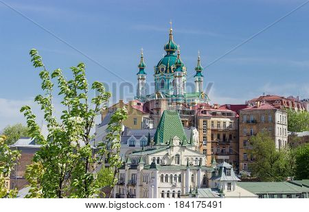 Baroque church Saint Andrew's built in the 18th century above other buildings with flowering tree in the foreground against the sky in Kiev Ukraine.