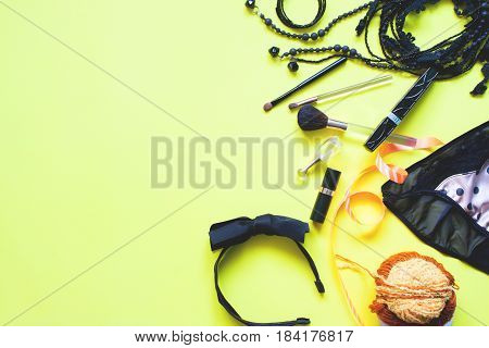 Flat lay of female asccessories in black and golden concept on yellow background Spring fashion concept with copy space