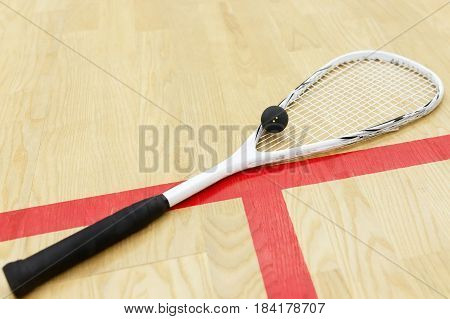 white squash racket and ball on the wooden floor. Racquetball equipment on the court near red line. Photo with selective focus