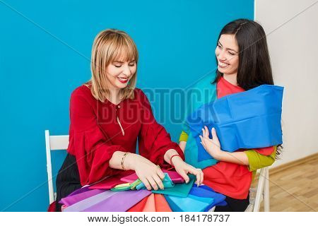 stylist doing color analysis of appearance for young woman. Image maker determines the colors that best suit an individual based on client natural colorings. Happy stylist holding colorful shawls