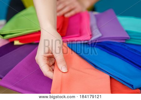 choosing a textile color. Samples of colorful fabric in hands of woman. Closeup view of female hand holding fabric color swatches