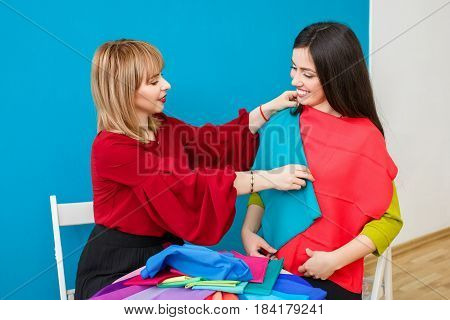 color analysis. Color type test. Image maker determines the colors that best suit an individual based on client natural colorings. Stylist working with young woman and holding colorful shawls