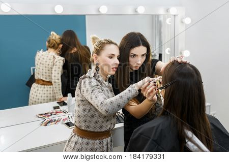 makeup teacher explaining for her student how to apply makeup properly. Makeup tutorial lesson at beauty school. Make-up artist working in studio.  Master class.