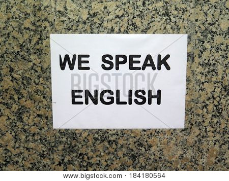 Sign on wall in Andalusian village announcing that We speak English