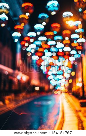 Defocused background of empty night city street with multiple bokeh circles of different colors beautiful colorful vertical view of blurred night lights on top during festival or celebration