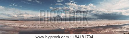 Scenery panorama of frozen sea during ice drift on springtime with dramatic sky and clouds having reflections in melt water on evening in Novosibirsk Russia