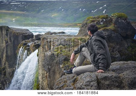Young man on the edge contemplating Godafoss waterfall. This waterfall is one of the best attraction on Iceland. Suitable for Earth's day environmental protection idea or similar.