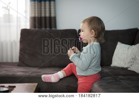 Cute little girl with pacifier in mouth sitting on a sofa and resting