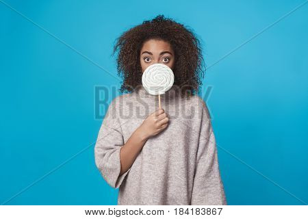 Young african woman studio portrait isolated on blue holding lollypop