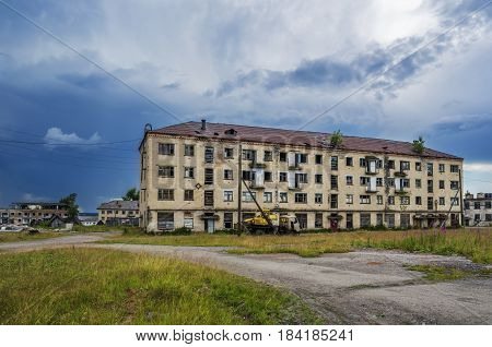 An abandoned house in a dying town of Yubileyny on the background of dark cloudy sky. Russia Perm Krai
