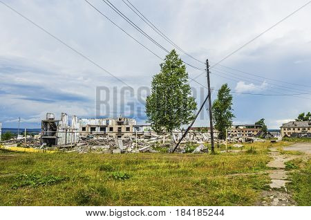 The ruins of a multistory building in the abandoned town of Yubileyny on the background of dark cloudy sky. Russia Perm Krai