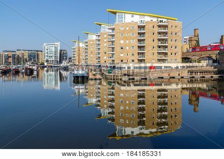 Waterside apartments at Limehouse Basin Marina in London with Docklands Light Railway passing in the background