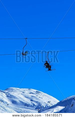 Unrecognizable skier on ski lift chair against clear blue sky