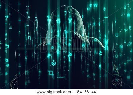 Hooded unrecognizable hacker and cyber criminal working on laptop programming bugs and viruses for computers matrix like code is overlaying image