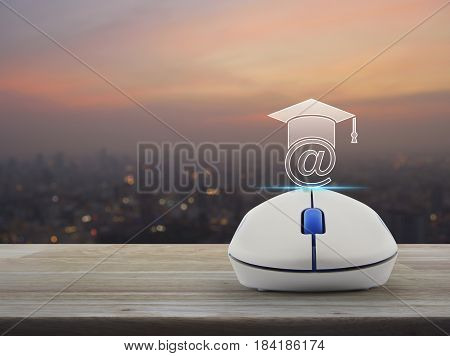 Wireless computer mouse with e-learning icon on wooden table over blur of cityscape on warm light sundown Study online concept