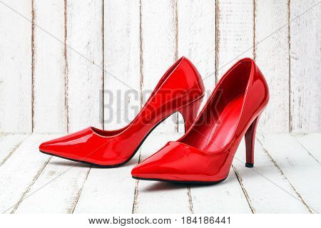 Red stiletto shoes on a wood background