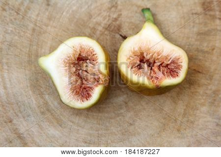 Common fig fruits cut open showing the flesh on wooden background ,Top view.