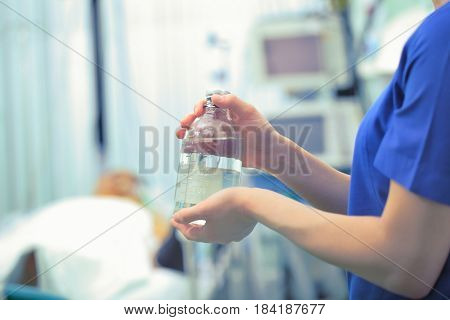 Transparent bottle in the hands of a nurse against the backdrop of a hospital ward