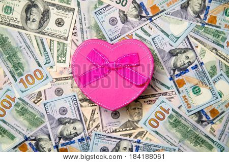 Gift box in the form of heart on a background of US currency