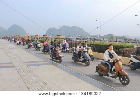 GUILIN CHINA - NOVEMBER 16, 2016: Unidentified people commute by electric motorbike.