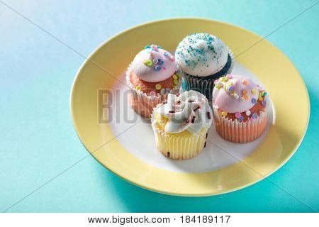 Delicious mini cup cakes decorated elegantly with icing sugar, arranged in a colorful plate.