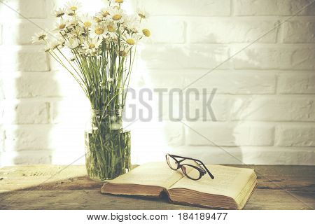 Chamomile flowers and glaases on book on table on brick wall background