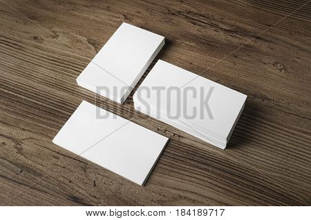 Mockup of three blank business cards stacks on wood table background. Blank template for your design.