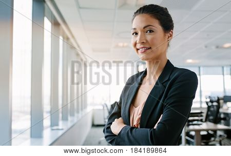 Portrait of mature businesswoman standing in office with her arms crossed and smiling. Asian female executive looking at camera confidently.