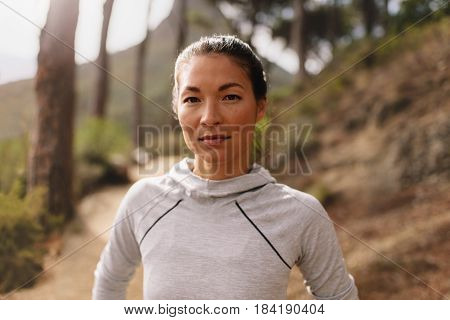 Portrait of young female athlete standing outdoors and looking at camera. Woman runner outdoors on country road taking a break after running exercise.