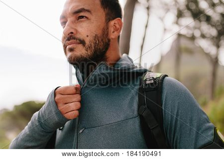 Portrait of healthy young man standing outdoors and looking away. Handsome young male runner in sportswear.