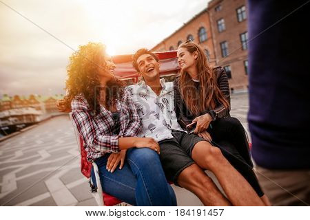 Cheerful teenage friends on tricycle. Young man and women riding on tricycle on road and having fun.