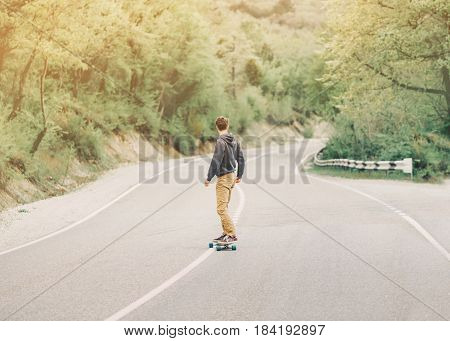 Young man riding a longboard on empty winding mountain road in summer rear view.