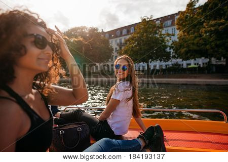 Shot of smiling young woman sitting on deck of boat with female friend in front. Two young women on boat in lake.