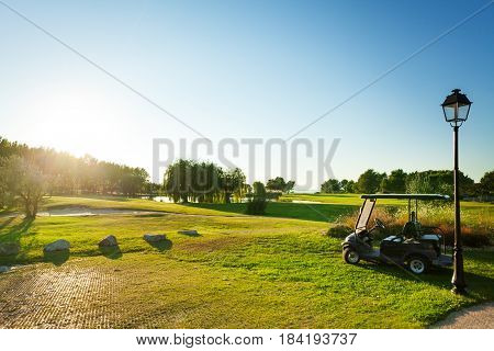 Panoramic view of green golf course with golf-cart in the foreground