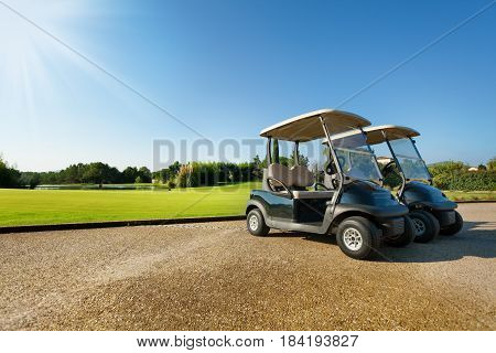 Two golf-carts standing at the parking lots against green golf course