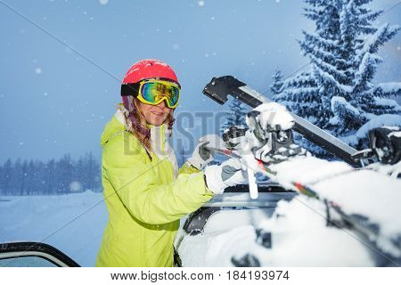 Portrait of young woman fastening skis on the roof of car after ski trip during snowfall