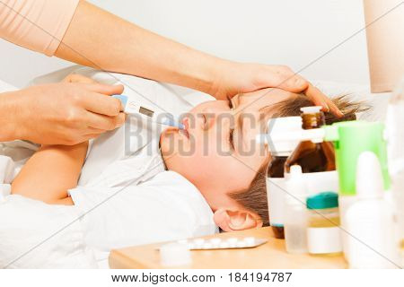Mother stroking her son's head and taking his temperature on electronic thermometer