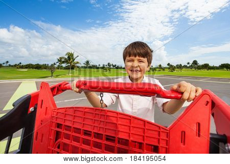 Portrait of happy kid boy pushing big red plastic shopping cart at supermarket parking lot
