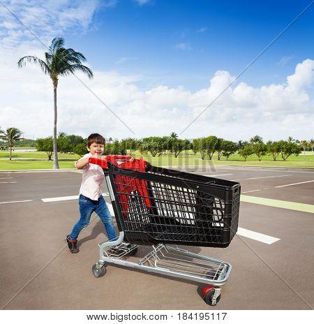 Cute boy pushing empty plastic shopping cart at parking lot