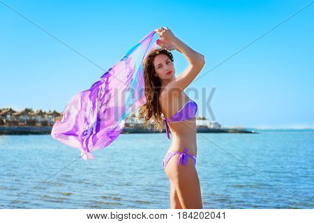 Young beautiful lady with curly hair playing with pareo against blue sky and sea background